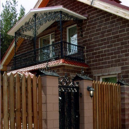 Балкон с коваными ограждениями и навесом.