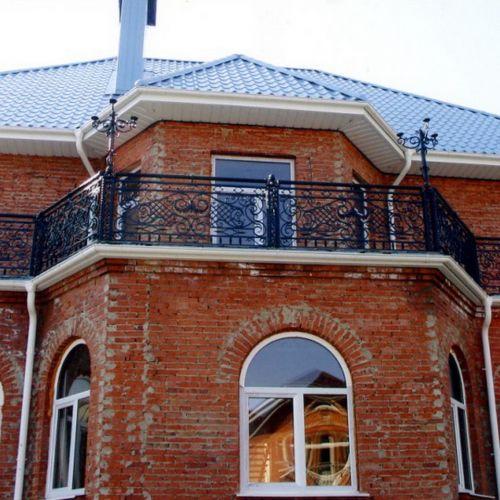 Балкон с кованым ограждением по периметру.