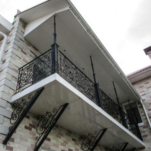Балкон с коваными ограждениями и консолями.