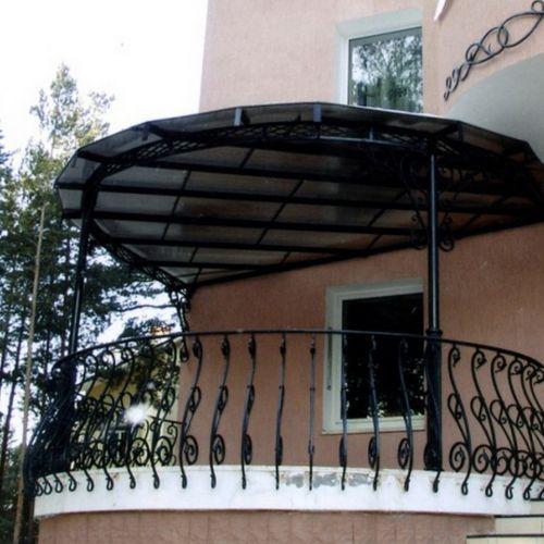 Круглый балкон с коваными ограждениями и навесом.