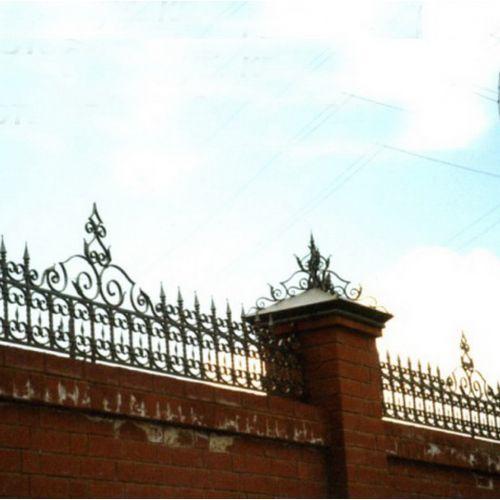 Забор, украшенный коваными колпаками и парапетом.