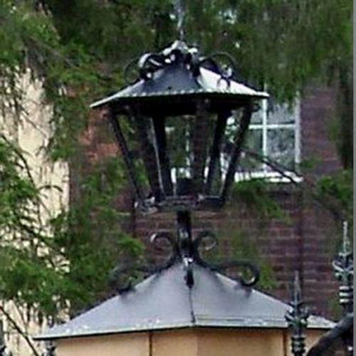 Кованый колпак-фонарь на столбах ограды.